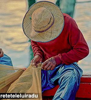 Pescar malaezian reparand plasele dupa o zi de munca